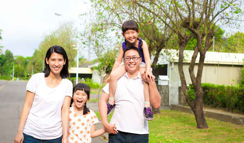 Young family of four, of East Asian heritage taking a walk in the neighborhood.